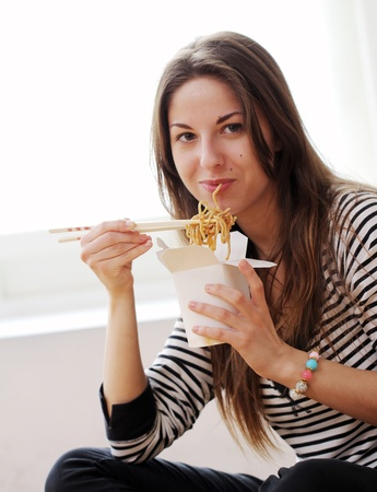 eating noodles: Happy woman eating noodles at home