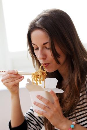 italienisches essen: Gl�ckliche Frau isst Nudeln zu Hause