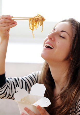 Happy woman eating noodles at home Stock Photo - 12931250
