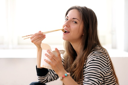 Happy woman eating noodles at home Stock Photo - 12931320