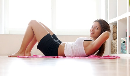 Young woman doing gymnastic exercises at home Stock Photo - 12931234