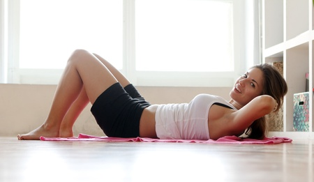 Young woman doing gymnastic exercises at home Stock Photo - 12931235