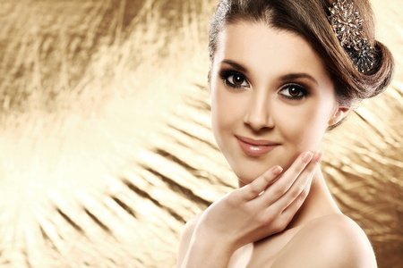 Beautiful woman with brooch in hair over golden background photo