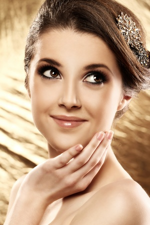 brooch: Beautiful woman with brooch in hair over golden background Stock Photo