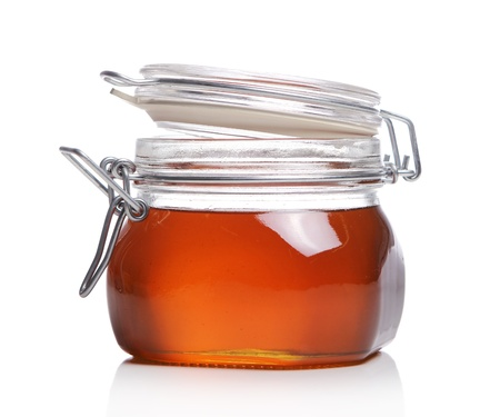 Jar with fresh honey over white background photo