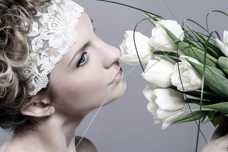 Beautiful young woman with white tulips over gray background Stock Photo - 13065751