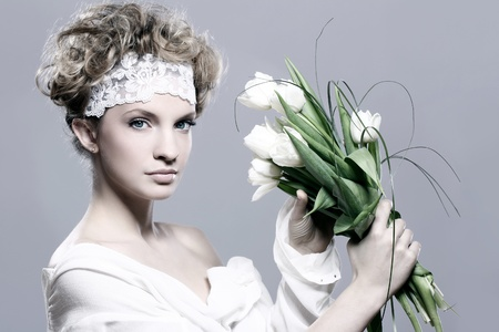Beautiful young woman with white tulips over gray background photo