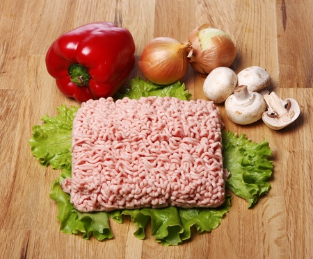 Minced meat and vegetables on wooden surface photo