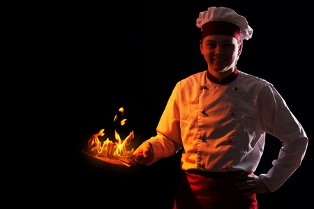Young chef holding pan with fire inside photo