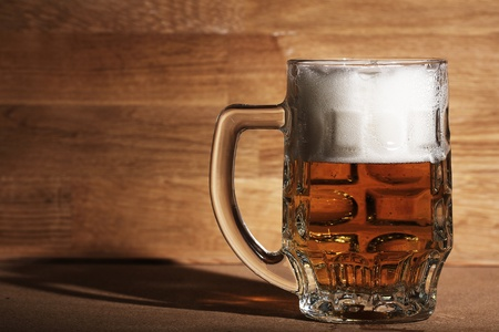 Glass of cold beer over wooden surface photo