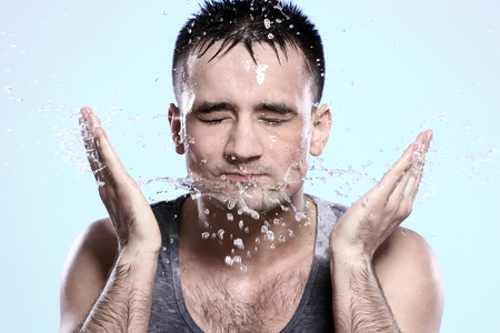 caucasian water drops: Handsome guy washing his face Stock Photo