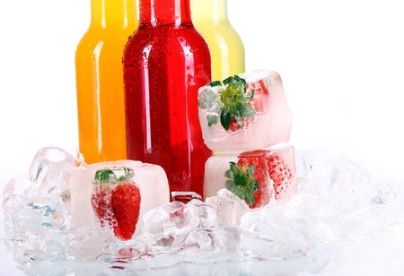 Bottles with colorful cocktail and ice over white background photo