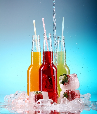 Bottles with colorful cocktails over blue background photo