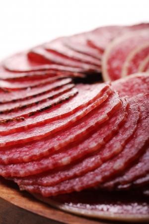 salame: Fette di salame fresco e delizioso su sfondo bianco Archivio Fotografico