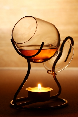 Glass of hot cognac over wooden surface photo