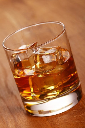Glass of cold whiskey on wooden surface photo