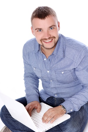 Handsome smiling guy with laptop sitting on the floor photo