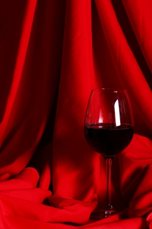 Glass of red wine over red cloth photo