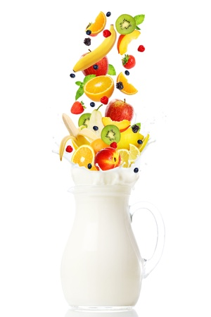 Fresh fruits falling into the jar with milk over white background photo