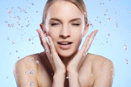 Young and beautiful woman washing her face photo