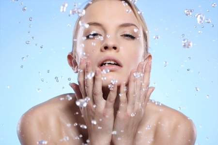 Young and beautiful woman washing her face Stock Photo