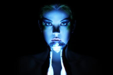 Beautiful woman with big jewel in darkness photo