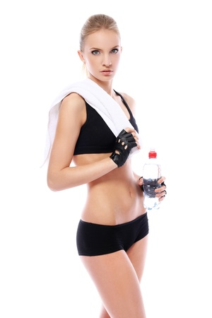 Beautiful fitness girl with towel and bottle of water over white background photo