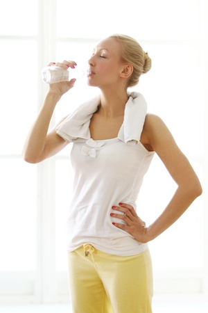 Beautiful woman drinking water after fitness workout photo