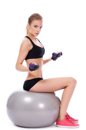 Beautiful woman doing exercises with dumbells on fitness ball over white background photo