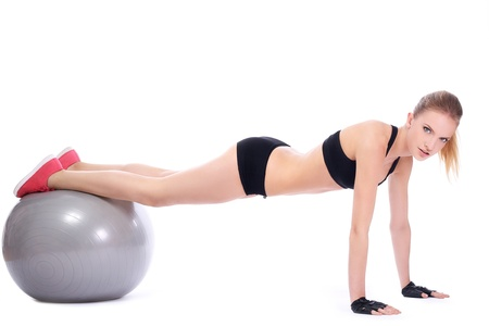 Beautiful woman doing push ups on fitness ball over white background  photo