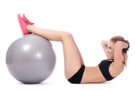 Beautiful woman doing abs exercises with fitness ball over white background photo