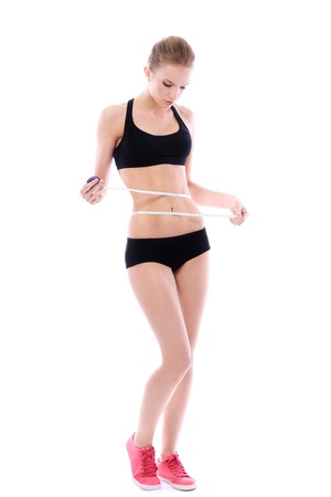 perfect fit: Beautiful woman measuring her waistline over white background  Stock Photo