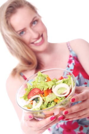 Happy woman with bowl of fresh salad over white background photo