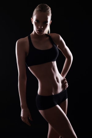 Beautiful girl with sexy body in darkness photo