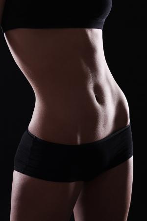 levantamiento de pesas: Est�mago delgado y sexy sobre fondo negro