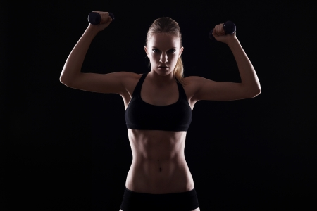Sexy woman doing exercises with dumbells over black background photo