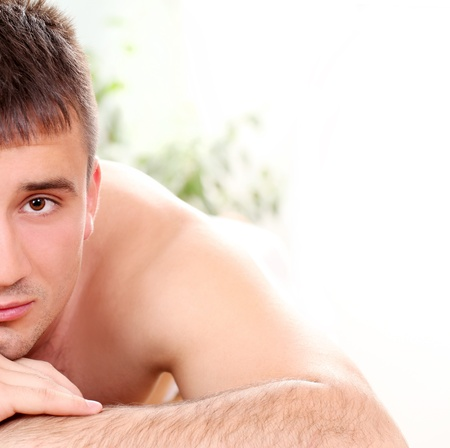 Handsome man relaxing and enjoying procedure of massage photo