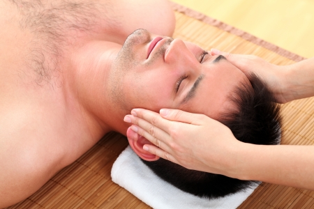 Handsome man enjoying face massage photo