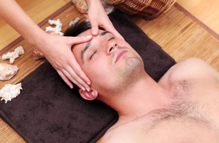 Handsome man enjoying face massage photo