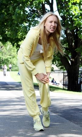 dolor de rodilla: Joven mujer se lesi�n en la pierna mientras trabajaba en el parque Foto de archivo