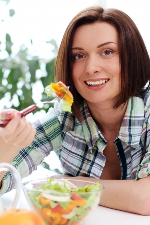 Happy woman with bowl of fresh and healthy salad photo