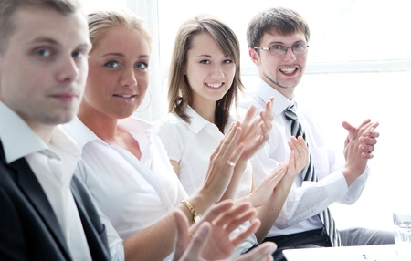 Businesspeople applauding during a business meeting Stock Photo