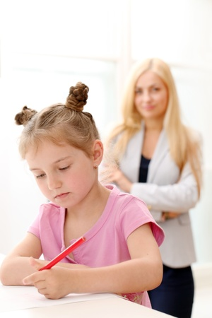 Older sister is teaching younger sister how to draw with a pencils photo