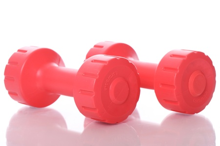 Small red dumbells over white background photo