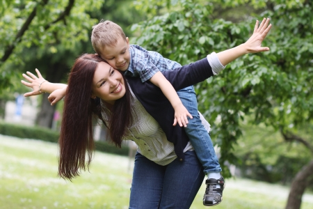 flowers boy: Young and happy mother with her son in the park Stock Photo
