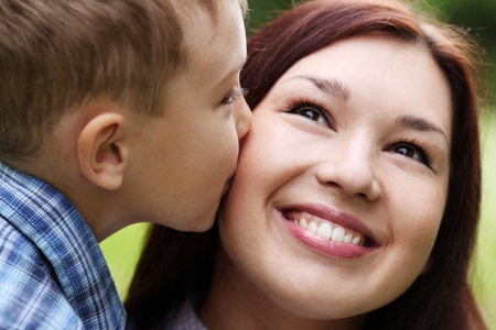 Boy kissing her mother at cheek photo