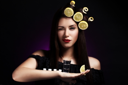 Sexy woman with lemons in her hairstyle  holding hot drink photo
