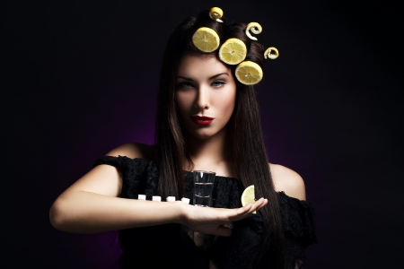 Sexy woman with lemons in her hairstyle  holding hot drink Stock Photo