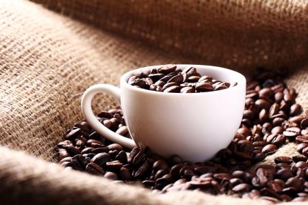 alubias: Copa llena de granos de café en la bolsa de tela