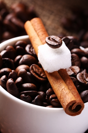Close up of cup with coffee beans and cinnamon stick photo